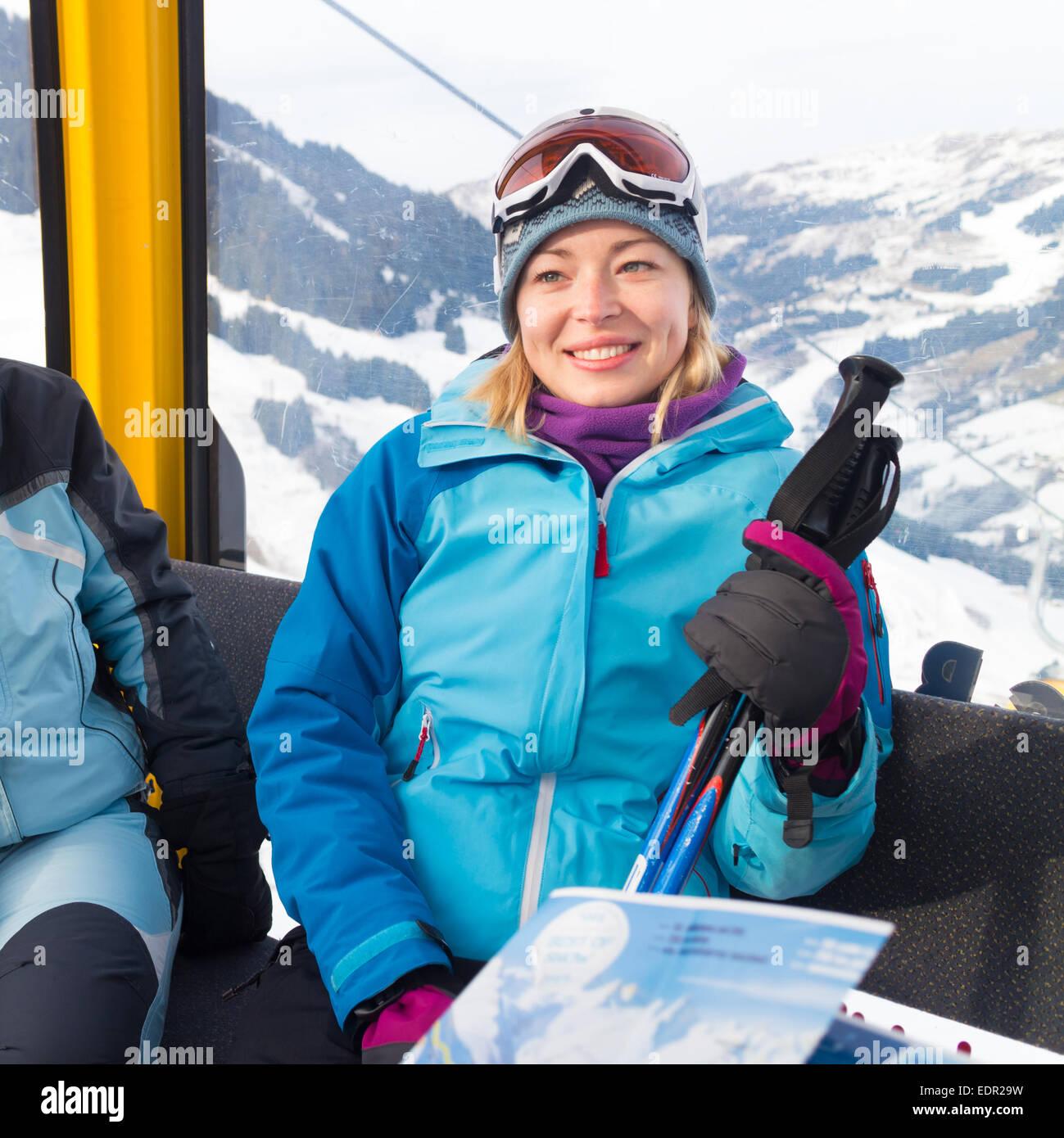 Female skier in gondola. - Stock Image