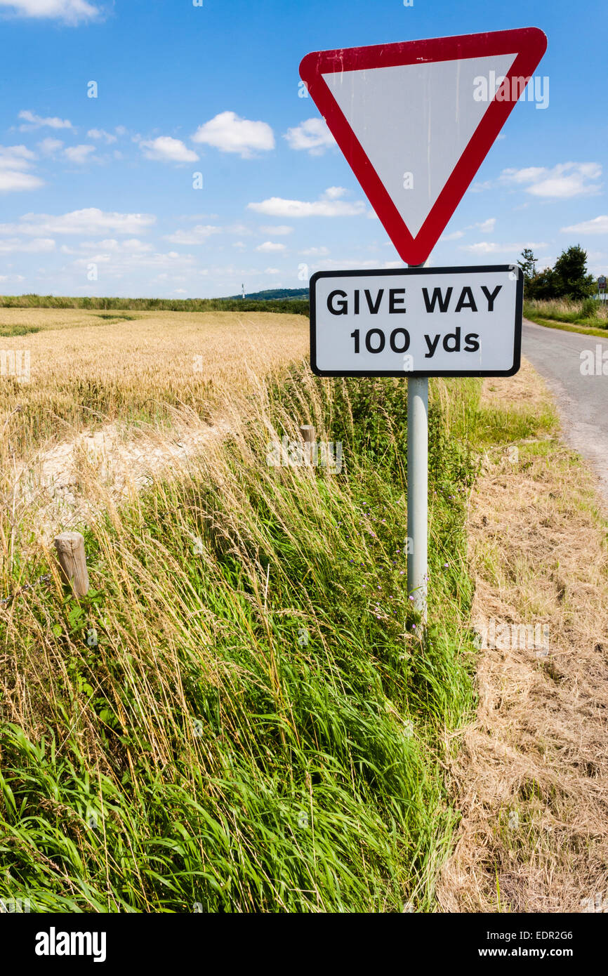 Give Way Sign by field on rural road in England. Stock Photo