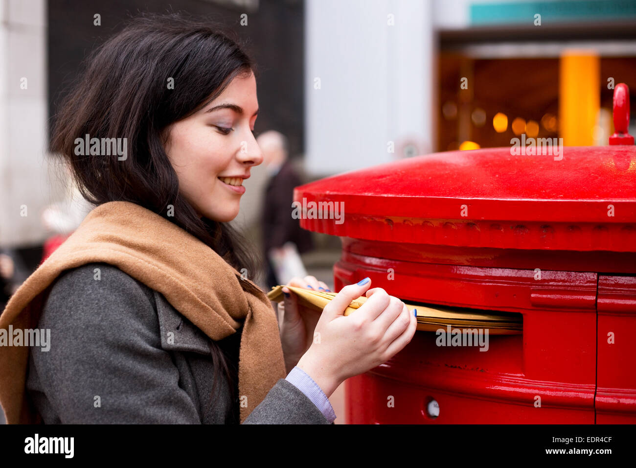 young woman posting letters - Stock Image