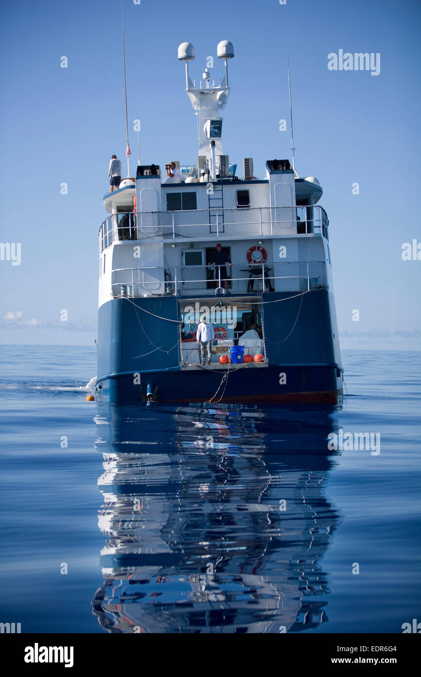a rear view of expedition boat floating on glassy blue water - Stock Image