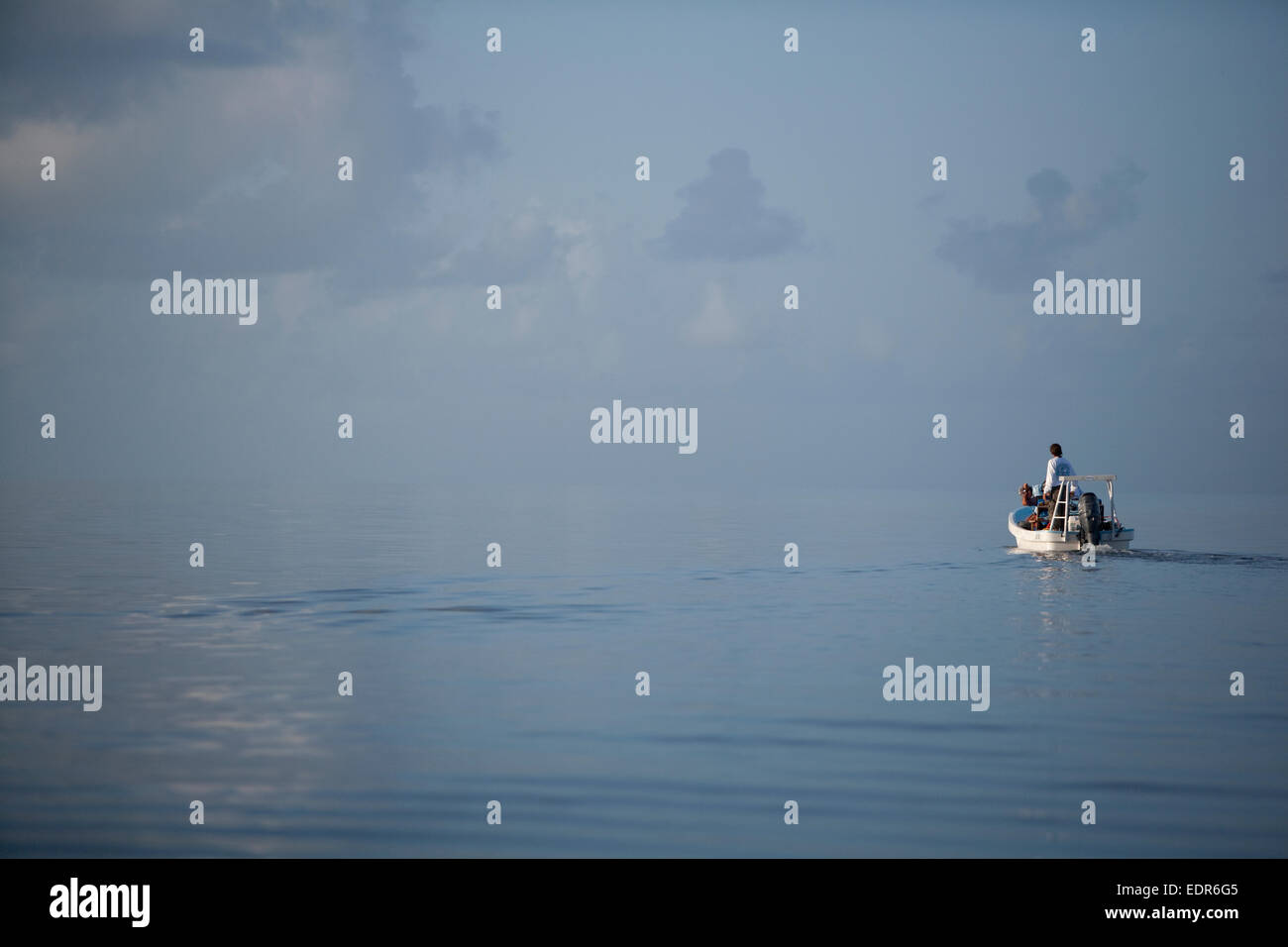 a flats boat motors out into calm ocean water - Stock Image