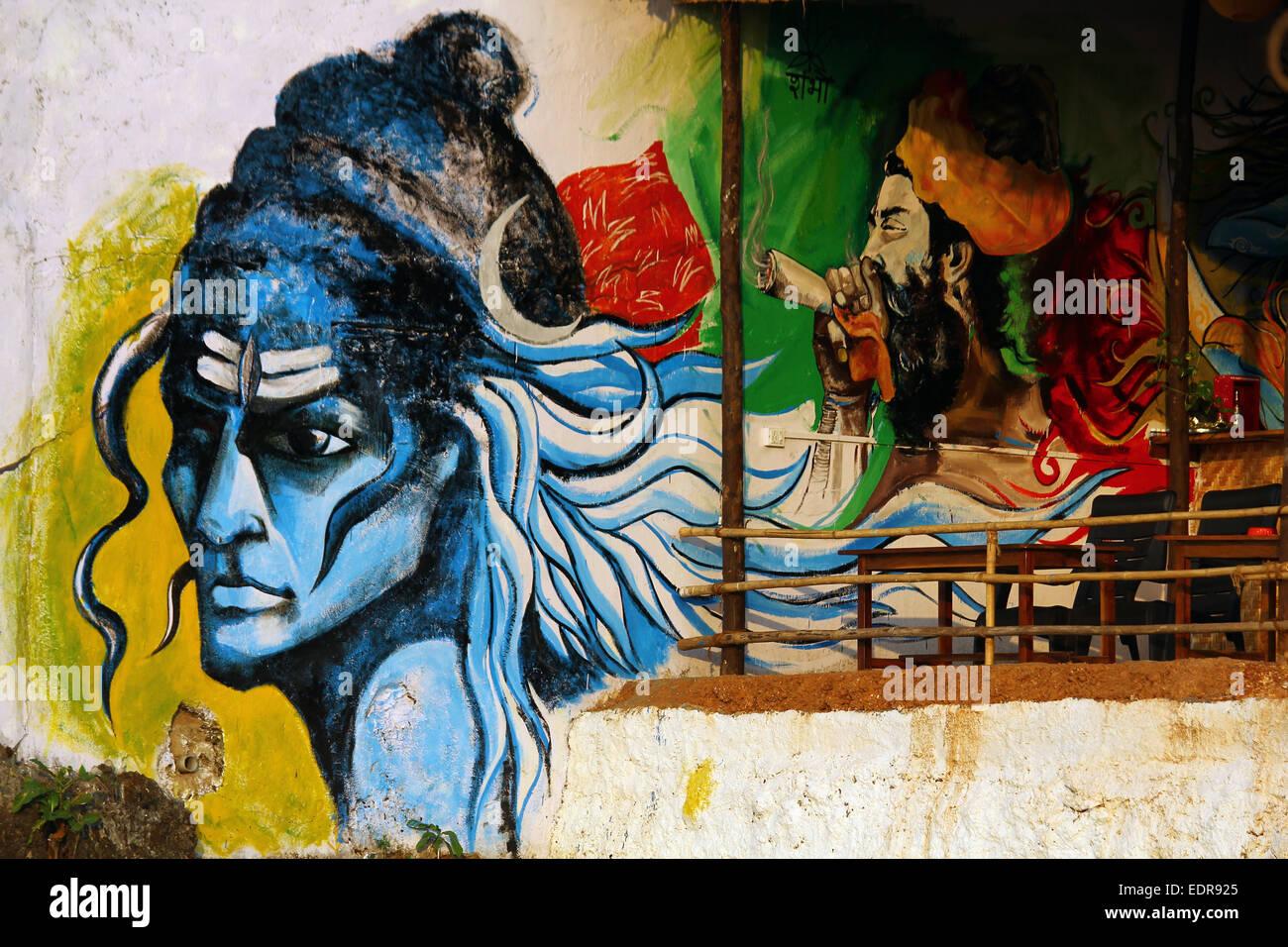 wall graffiti of hindu lord shiva and a man smoking marijuana - Stock Image