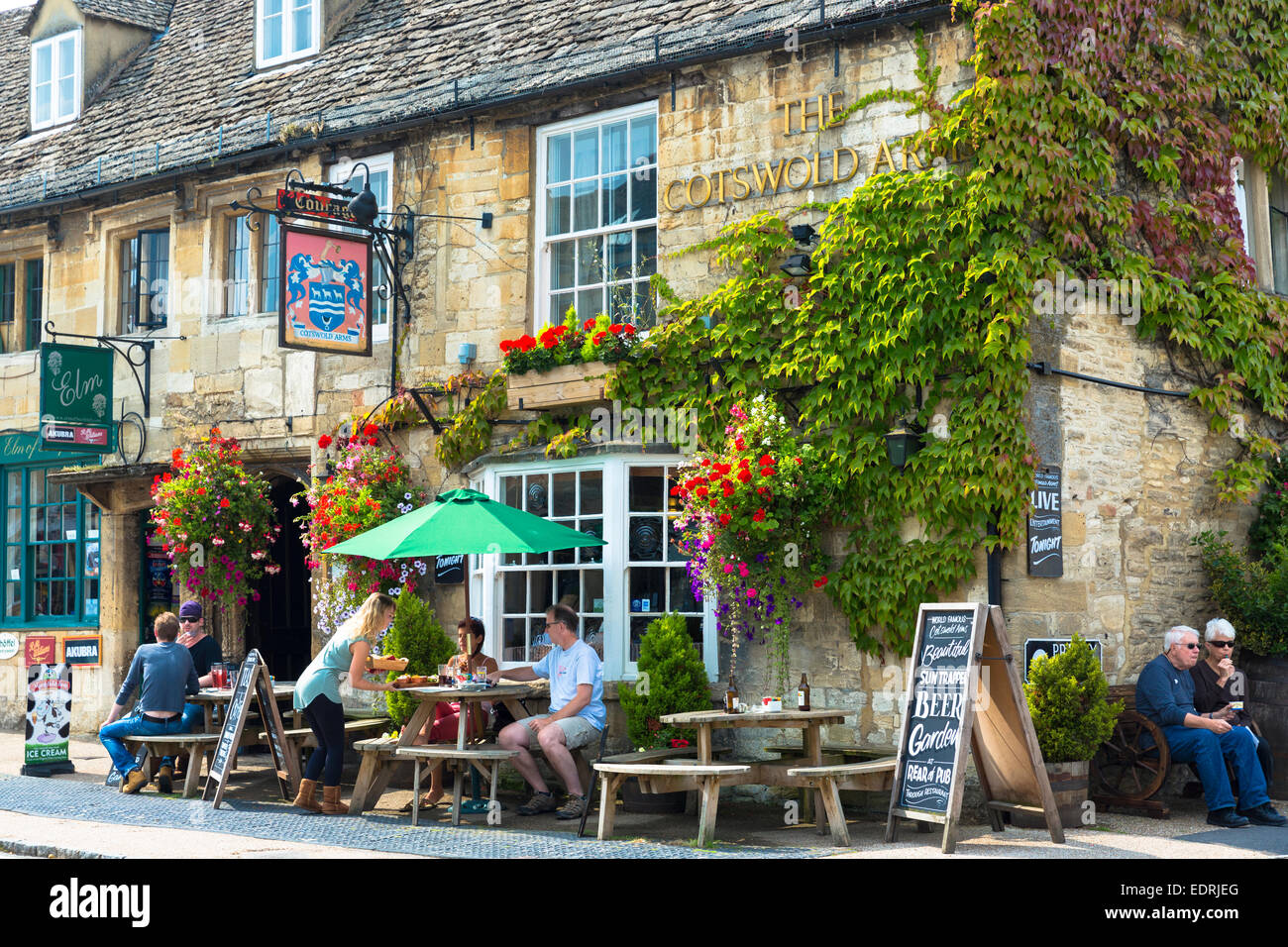 Tourists at The Cotswolds Arms inn traditional old gastro pub  in Burford in The Cotswolds, Oxfordshire, UK - Stock Image