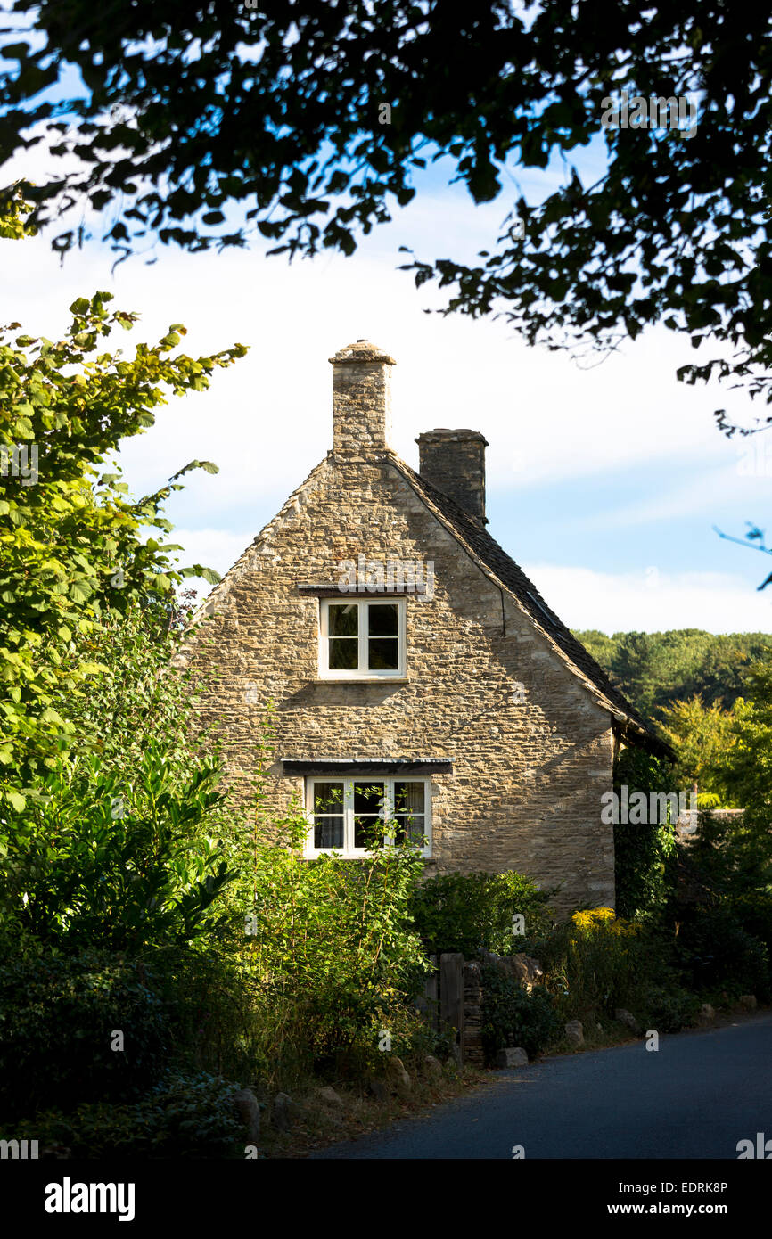Traditional and typical old stone country cottage by country lane at Swinbrook in the Cotswolds, England, UK - Stock Image