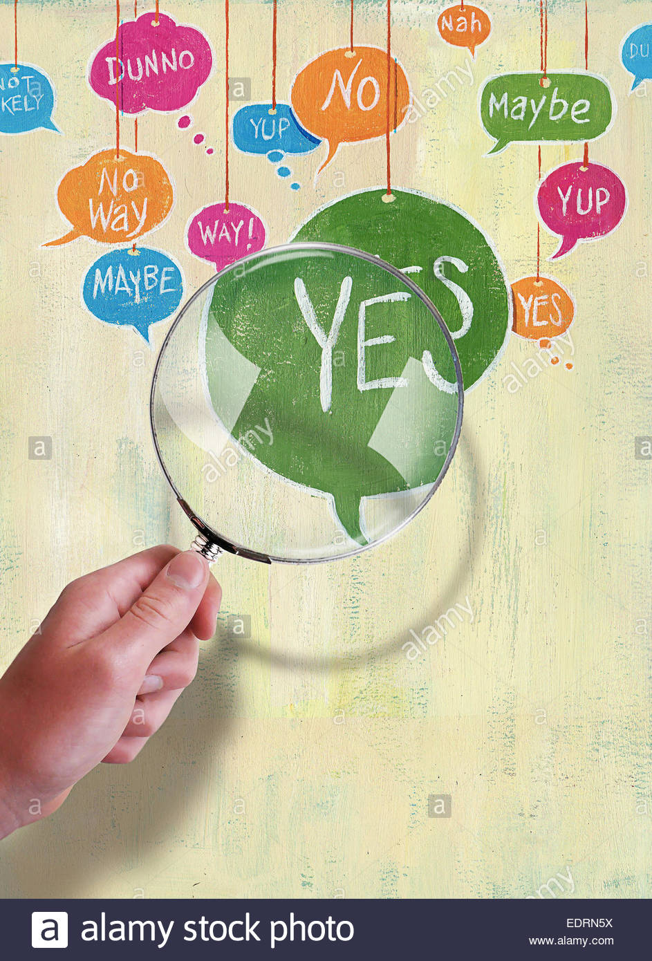 Hand holding magnifying glass over yes, no, maybe speech bubbles - Stock Image