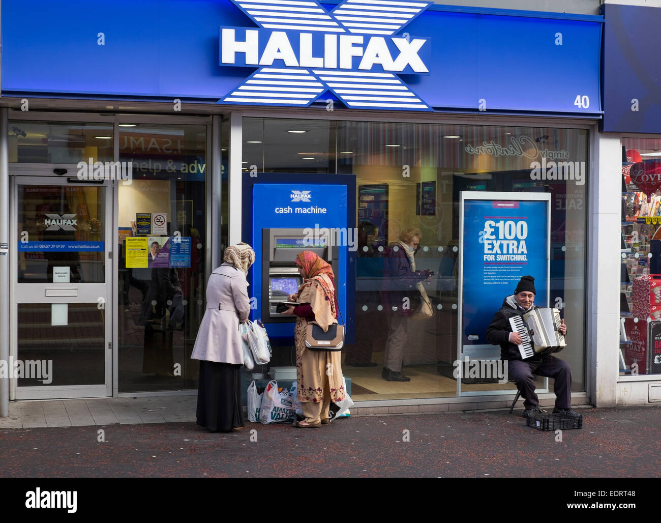 Two female shoppers using a cash machine and a busker with accordion outside Halifax UK bank in Walsall, West Midlands, - Stock Image