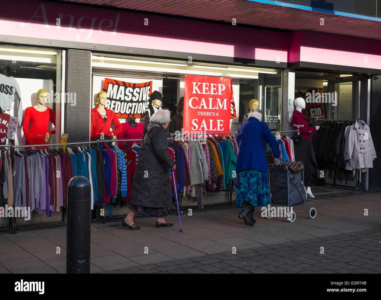 Two elderly women walk past a clothing shop with sale signs, Walsall, West Midlands, England. - Stock Image