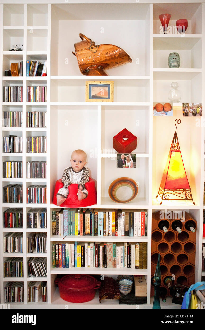 Baby sitting in a baby sitter in a bookshelf - Stock Image