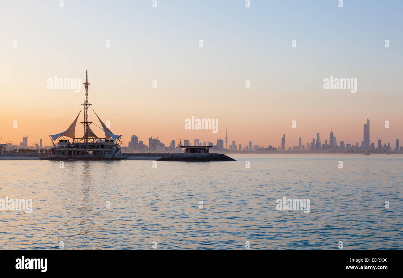 Skyline of Kuwait and Marina Waves pavilion at sunset - Stock Image