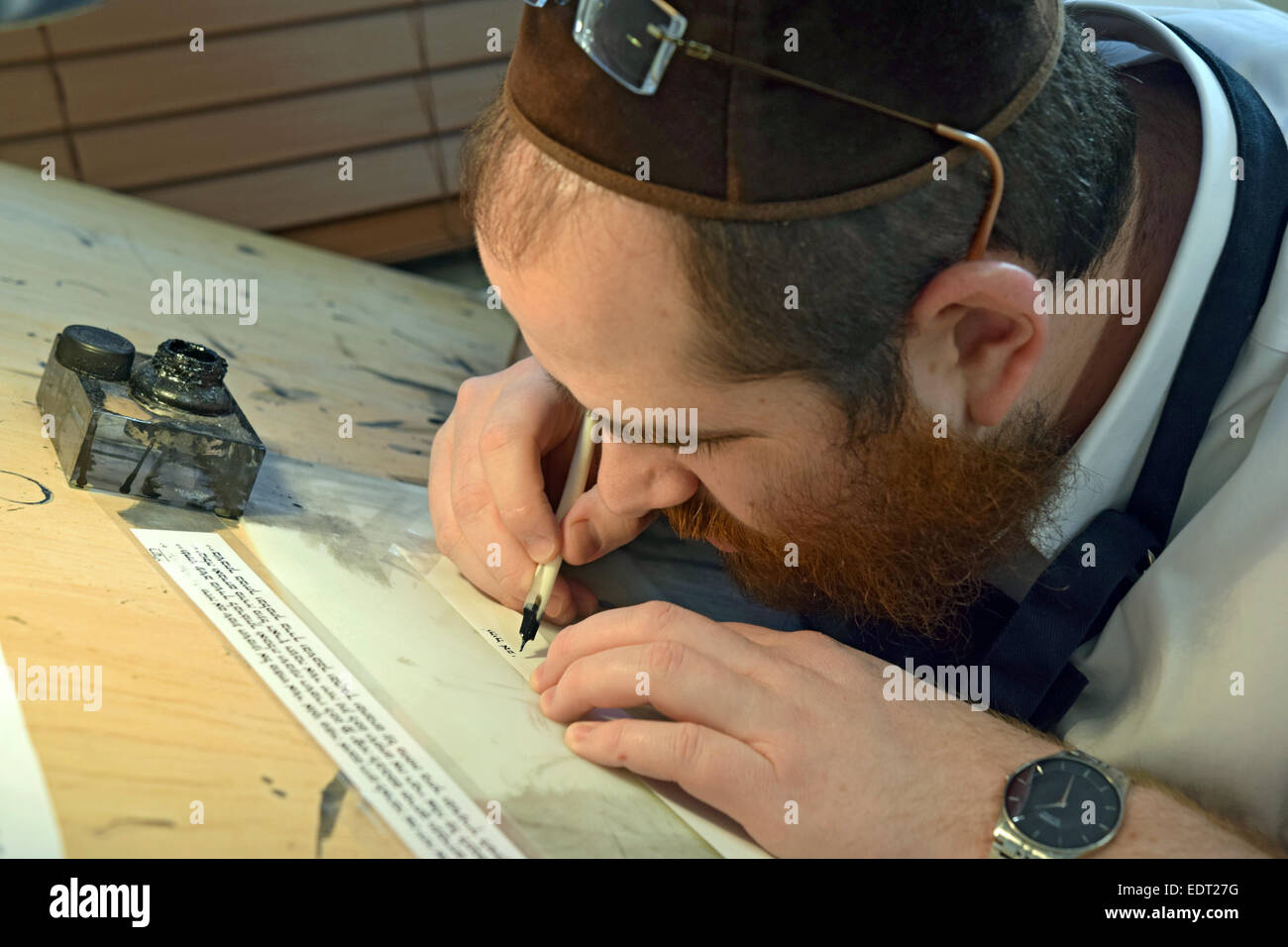 A religious Jewish scribe writing on parchment with a quill pen. The writings are used in phylacteries - teffilin. - Stock Image