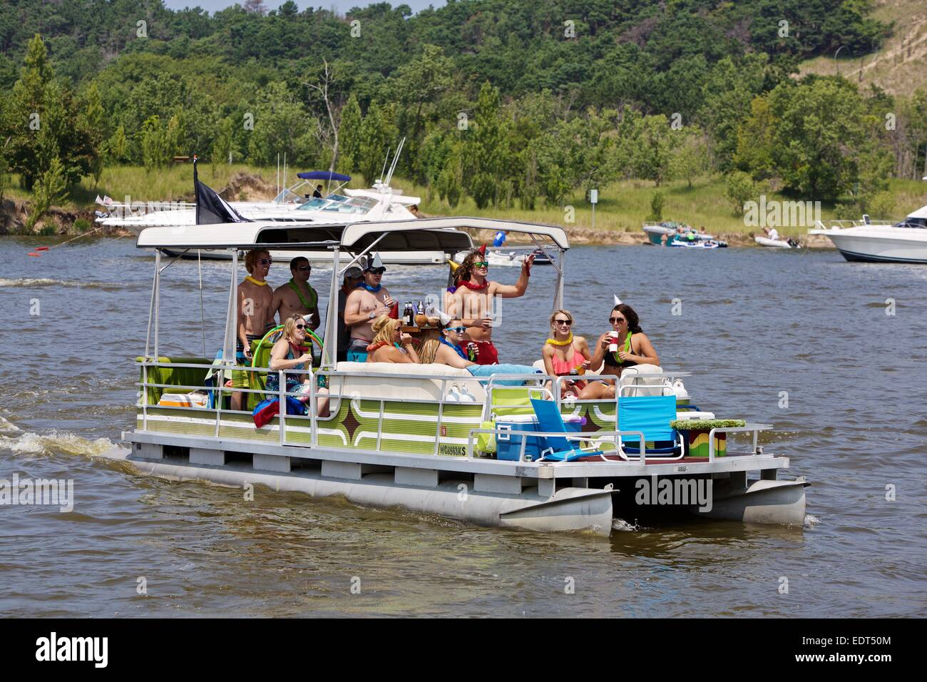 Revelers partying on a pontoon on the Grand River in Grand Haven, Michigan during the Coast Guard Festival - Stock Image