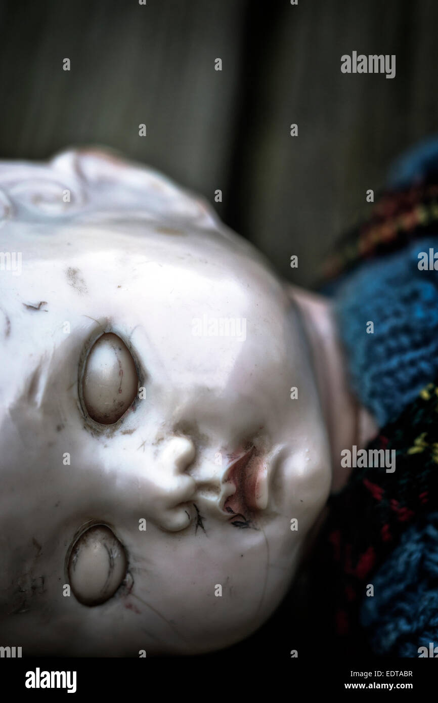 an old and broken doll with closed eyes - Stock Image