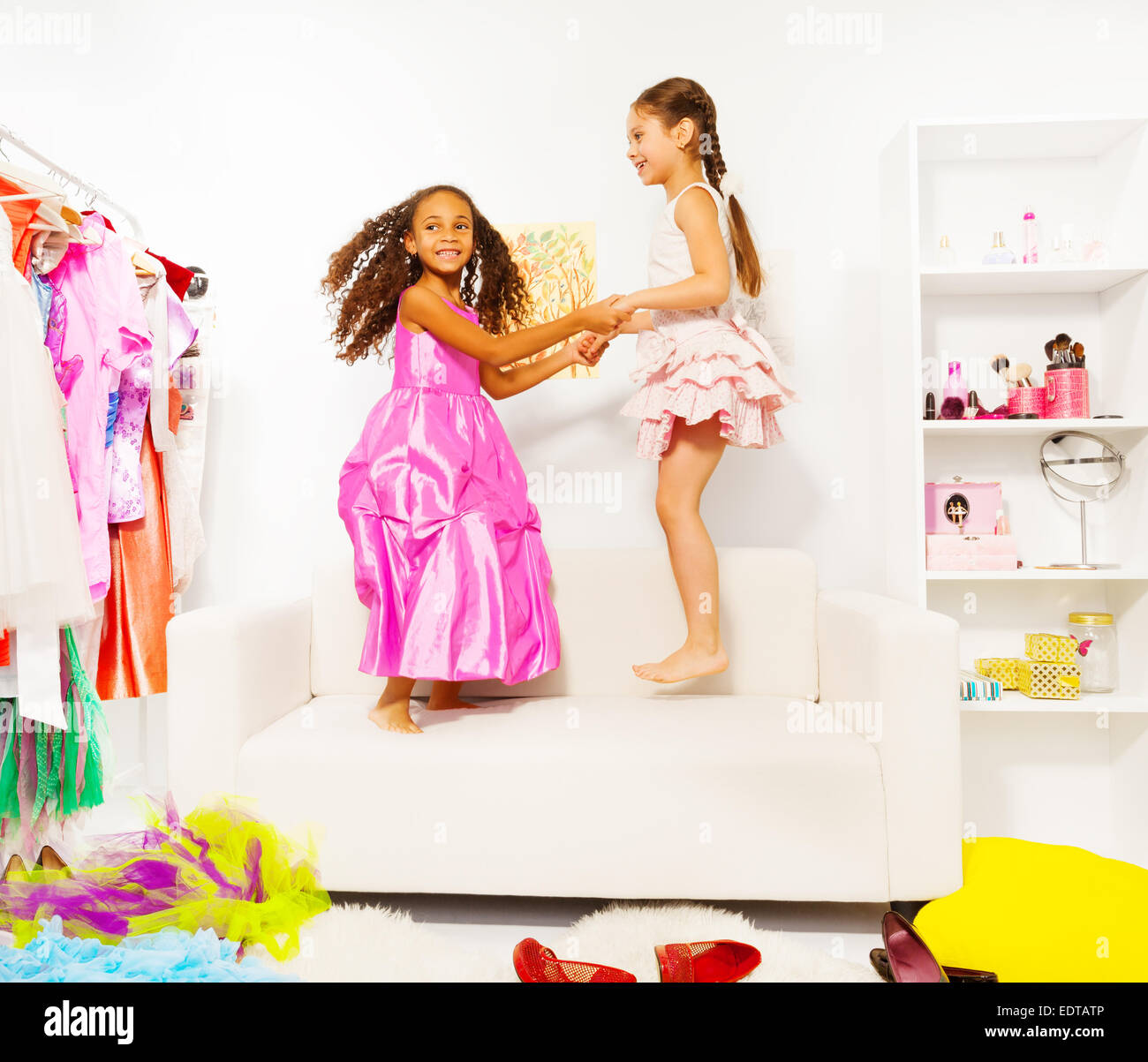 Two excited girls hold hands and jump together - Stock Image