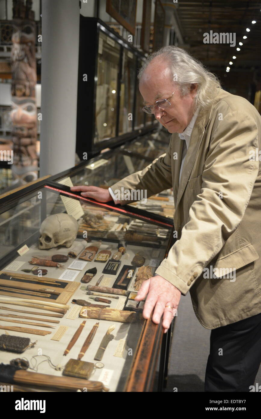 Philip Pullman examines ethnic  artifacts and trepanned skull at the Pitt Rivers Museum, Oxford, which inspired - Stock Image