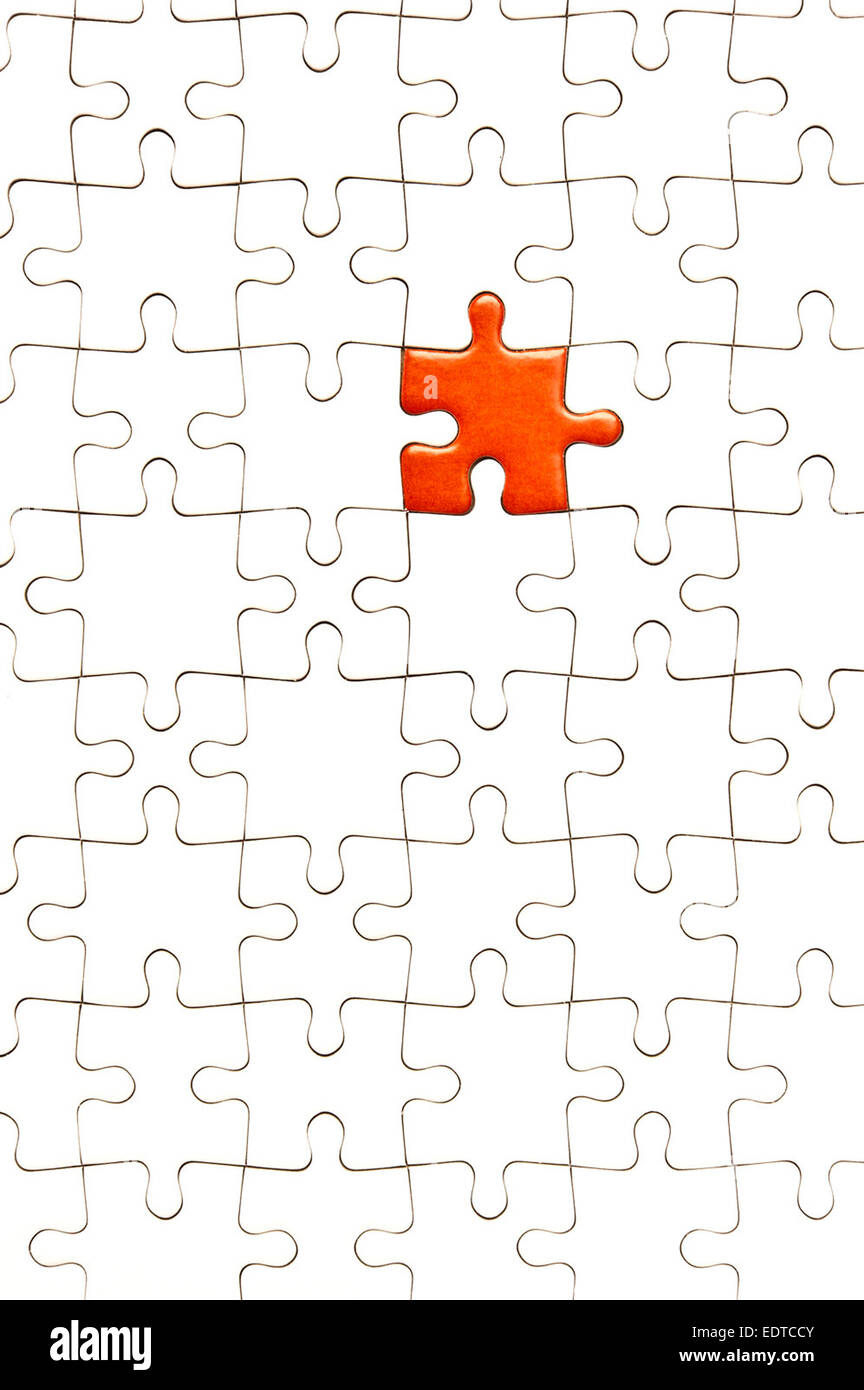 white jigsaw puzzle with one piece red - Stock Image