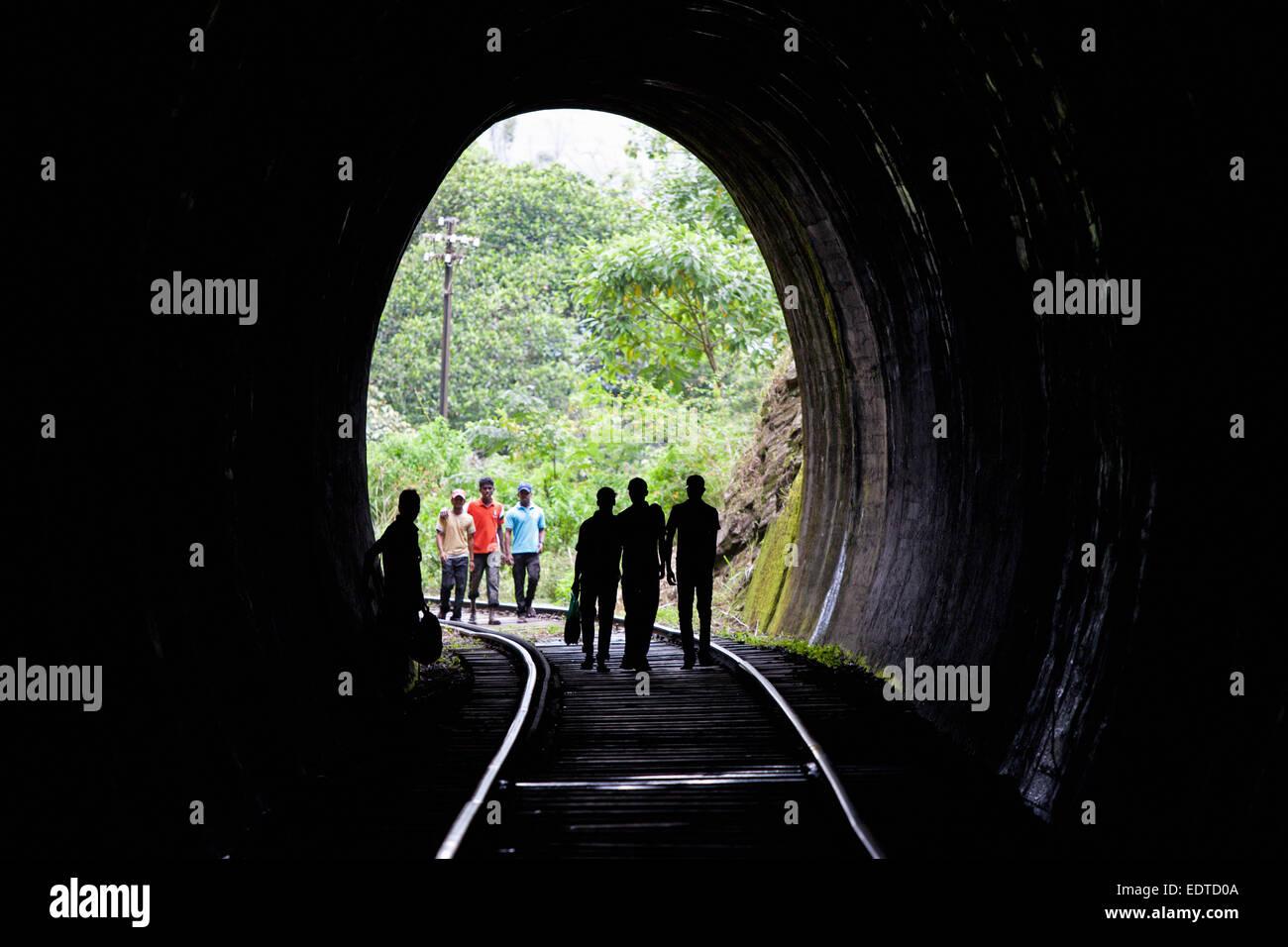 SRI LANKAN PEOPLE WALKING THROUGH TRAIN TUNNEL NEAR ELLA - Stock Image