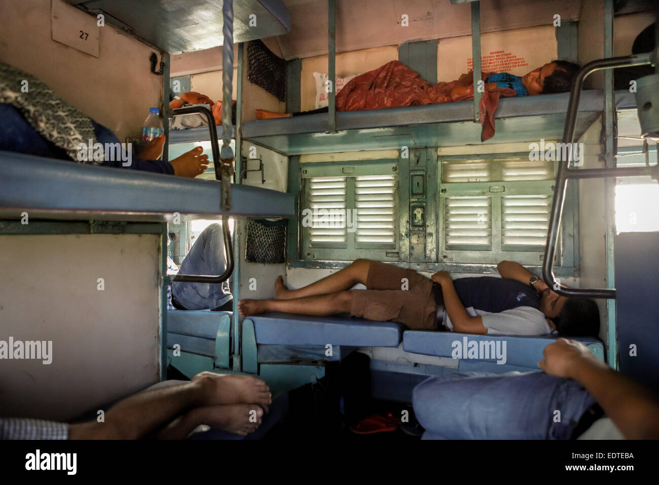 Passengers sleeping in sleeper class of the India railway service. - Stock Image