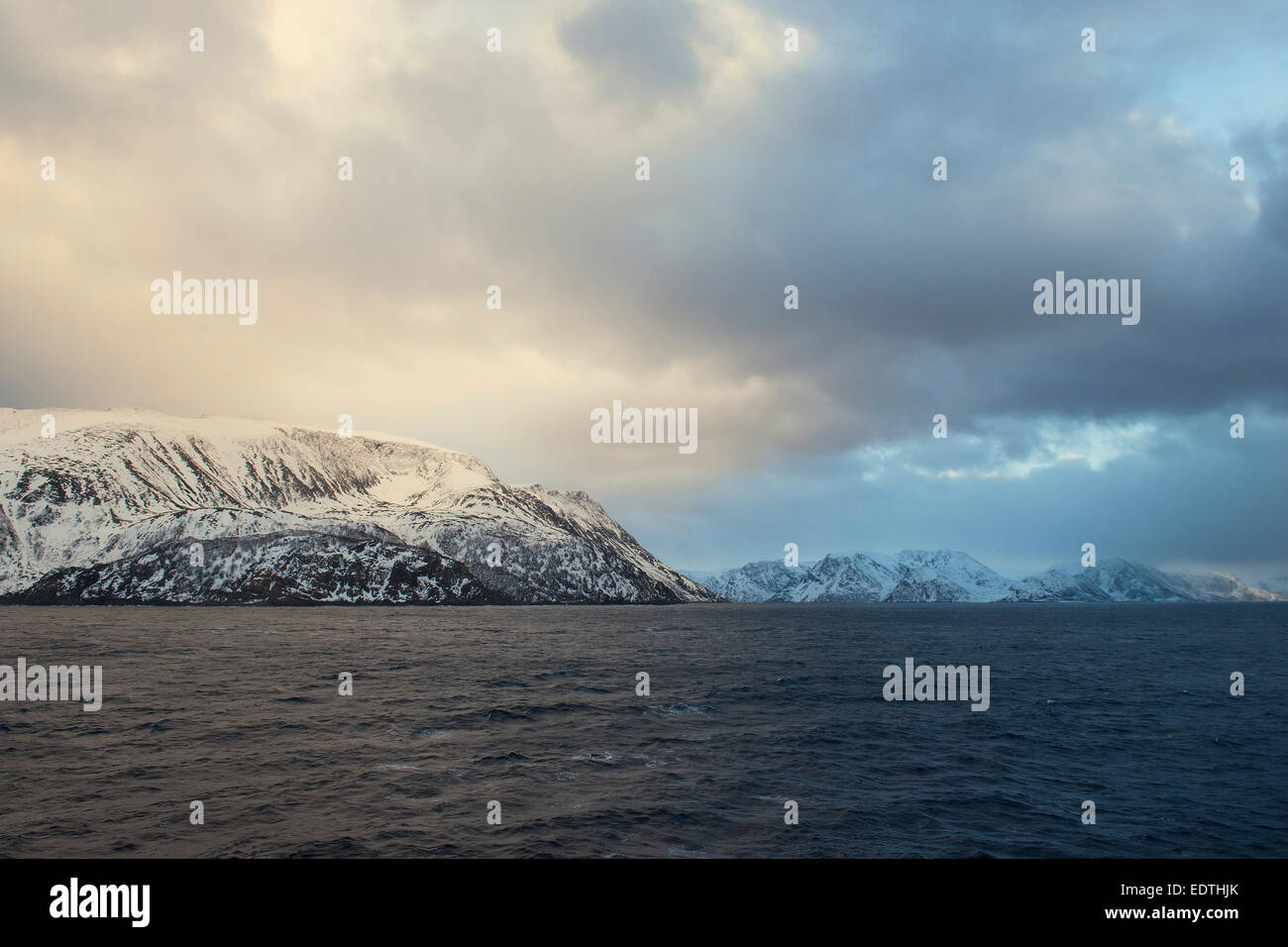 Snow covered rocky islandStjernøya under colourful lighted clouds, 25 February 2014 Stock Photo