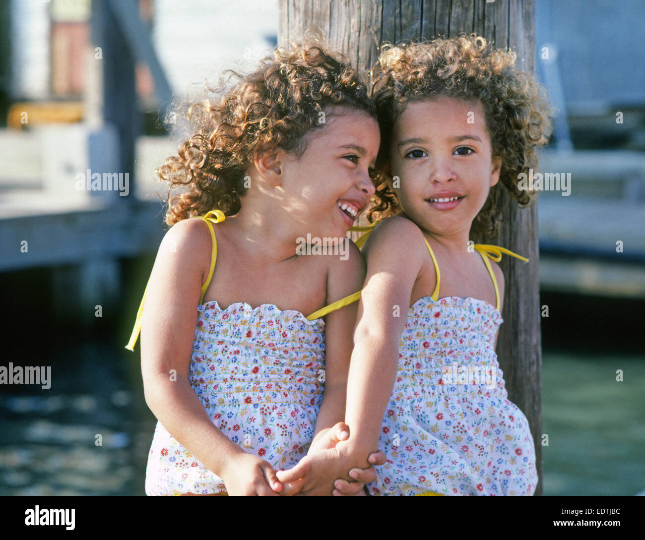 Two young black identical twins sitting on a dock on padre island texas stock