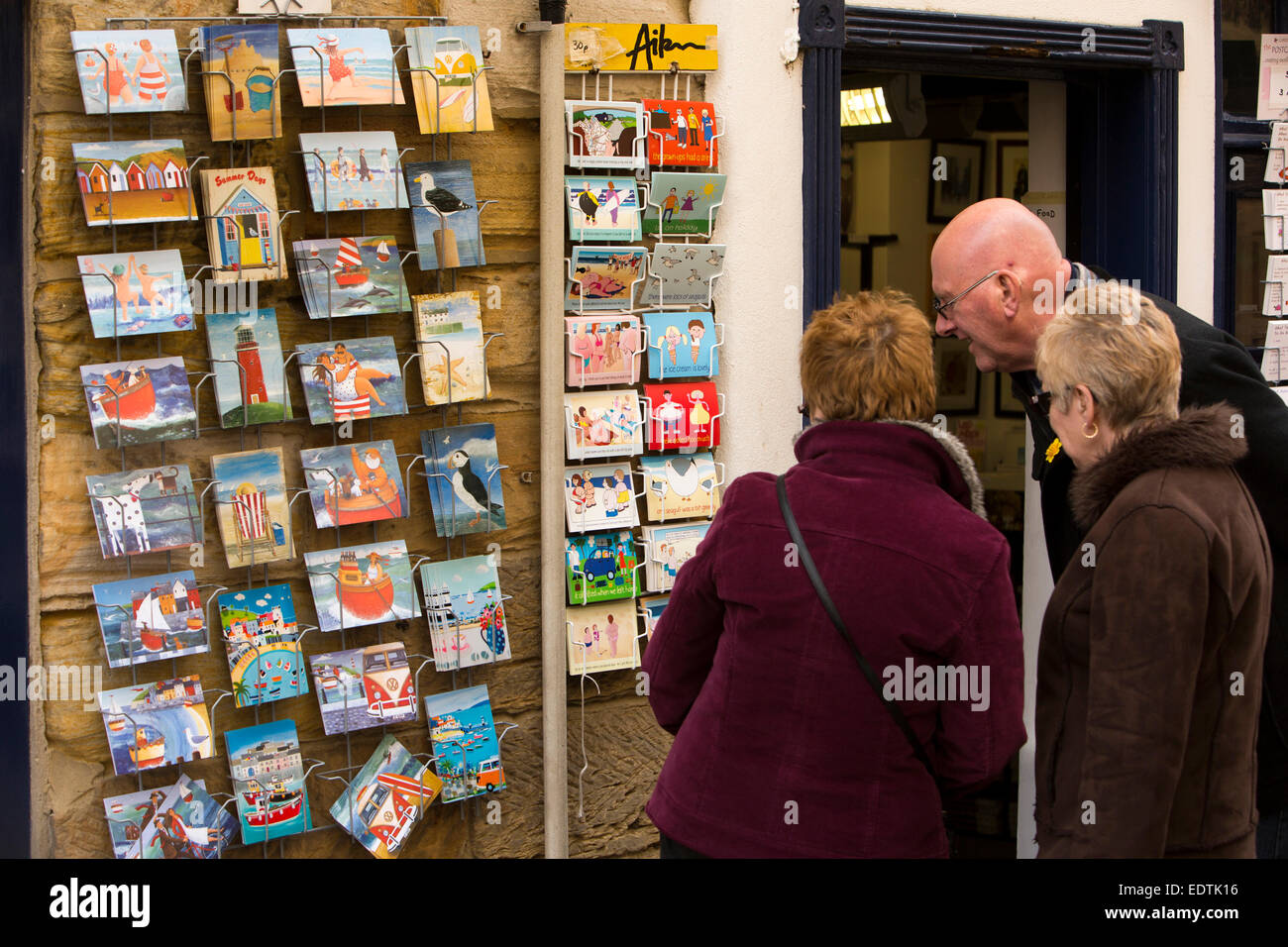 UK, England, Yorkshire, Whitby, Church Street, visitors looking at humorous picture postcard display - Stock Image