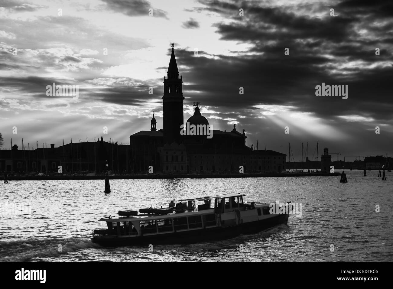 Church of San Giorgio Maggiore at sunset on the island of the San Giorgio Maggiore and a boat with tourists passing - Stock Image