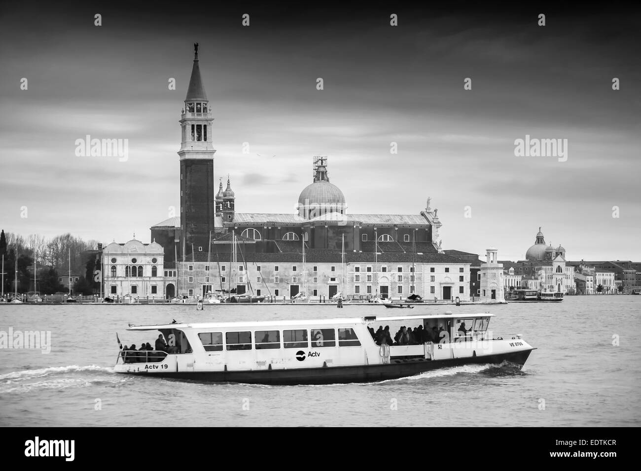 A boat with tourists passing in front of the Church of San Giorgio Maggiore - Stock Image