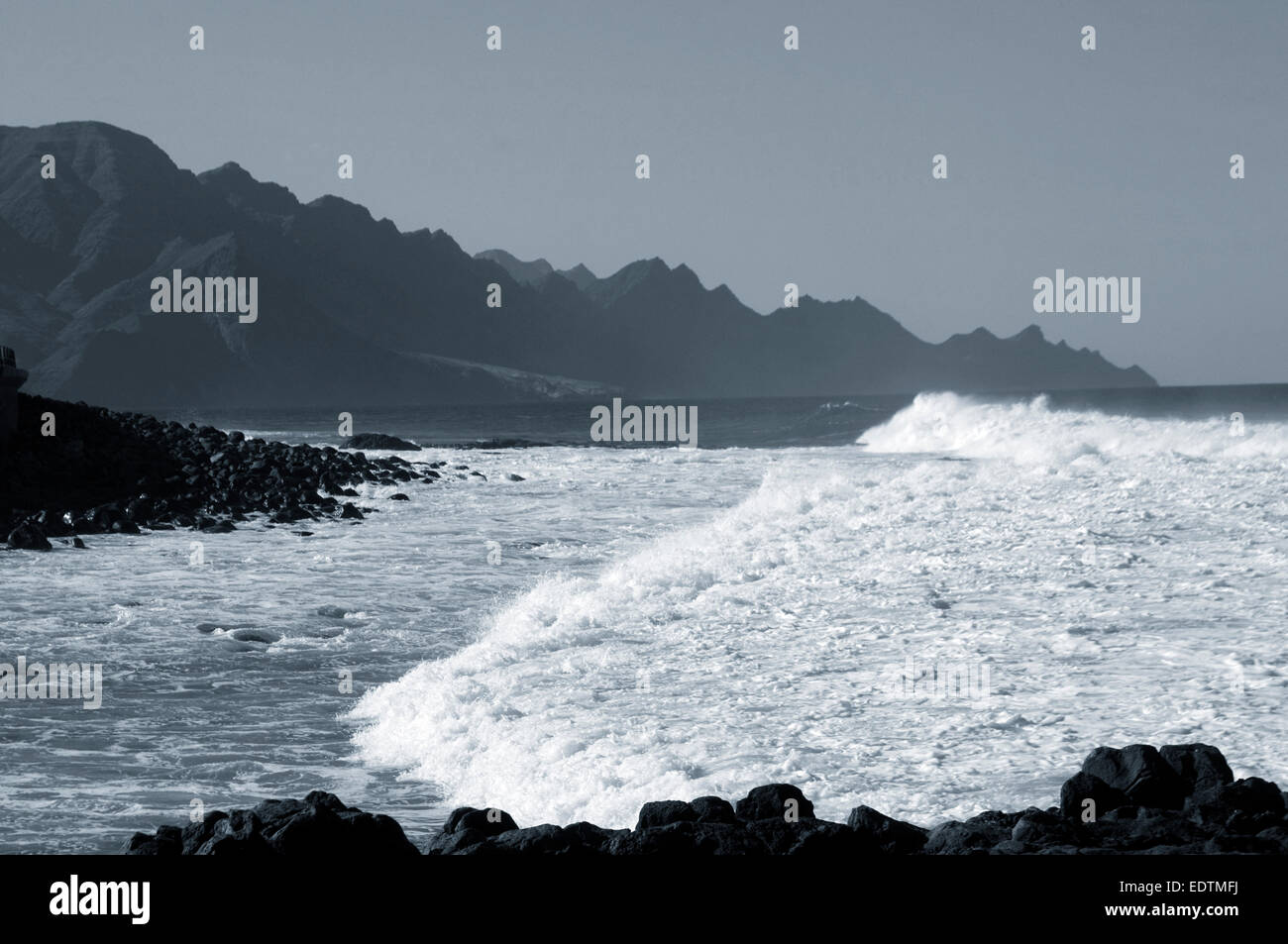 rocky craggy coastline of gran canaria canary islands canaries isles rough sea seas white foam foaming wave waves - Stock Image