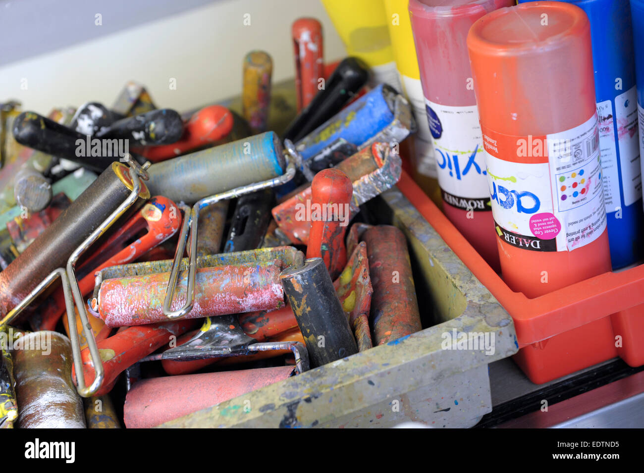 Silk screen rollers and acrylic paint pots in a school art room - Stock Image