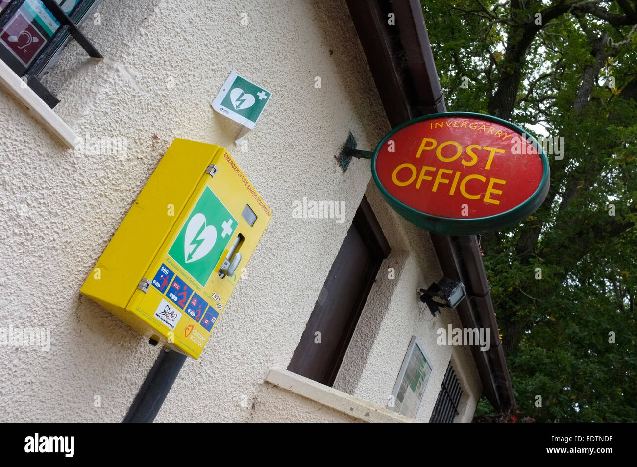 Public access defibrillator (PAD) on wall of rural post office in Scotland - Stock Image