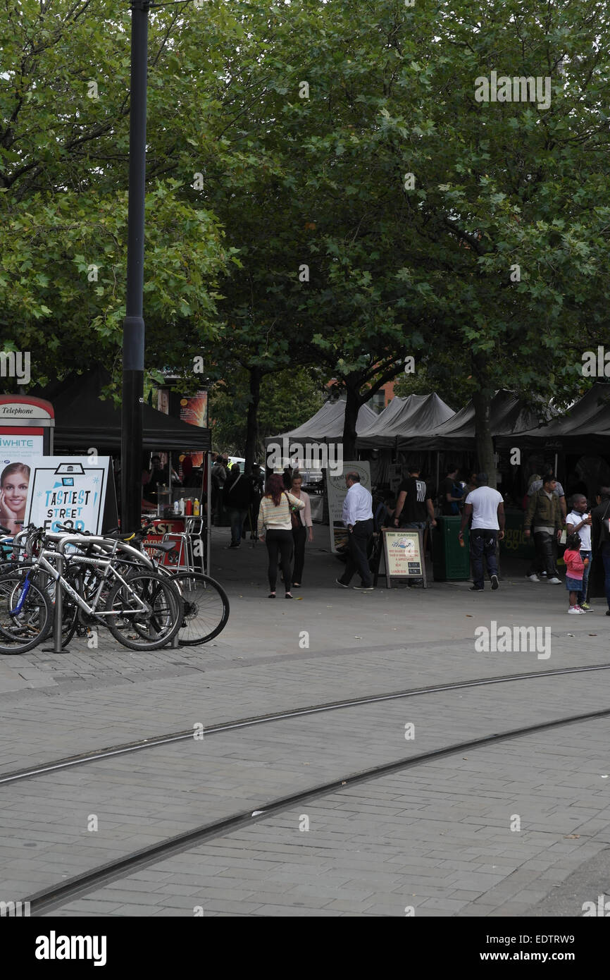 Portrait from Market Street walkway with tram line, people walking Piccadiily Street Food Market stalls, below trees, - Stock Image