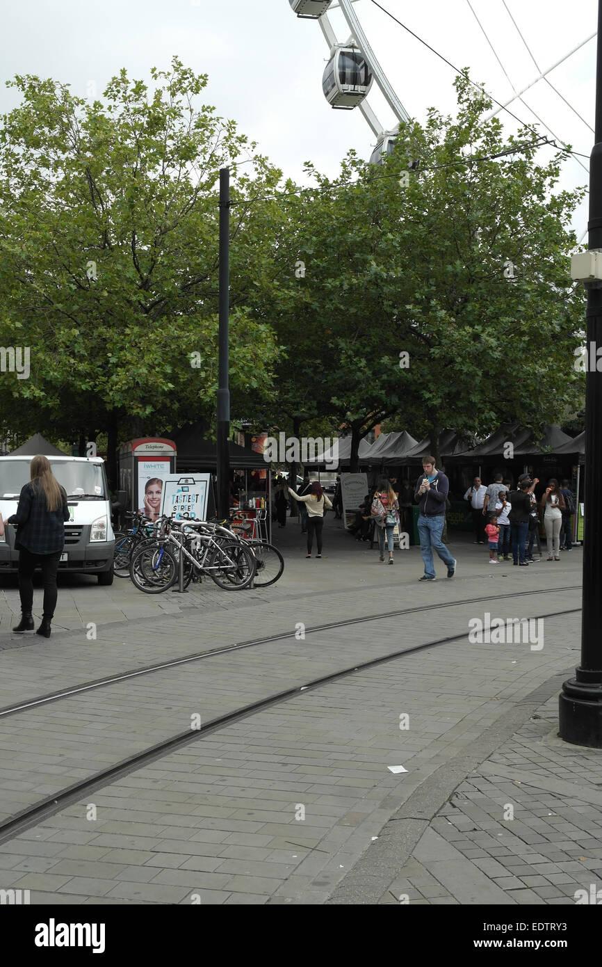 Grey sky portrait Market Street walkway tramway to people walking Piccadilly Street Food Market stalls below trees, - Stock Image