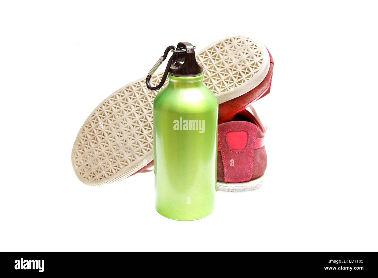 green metal bottle for drinks with sport shoes Stock Photo