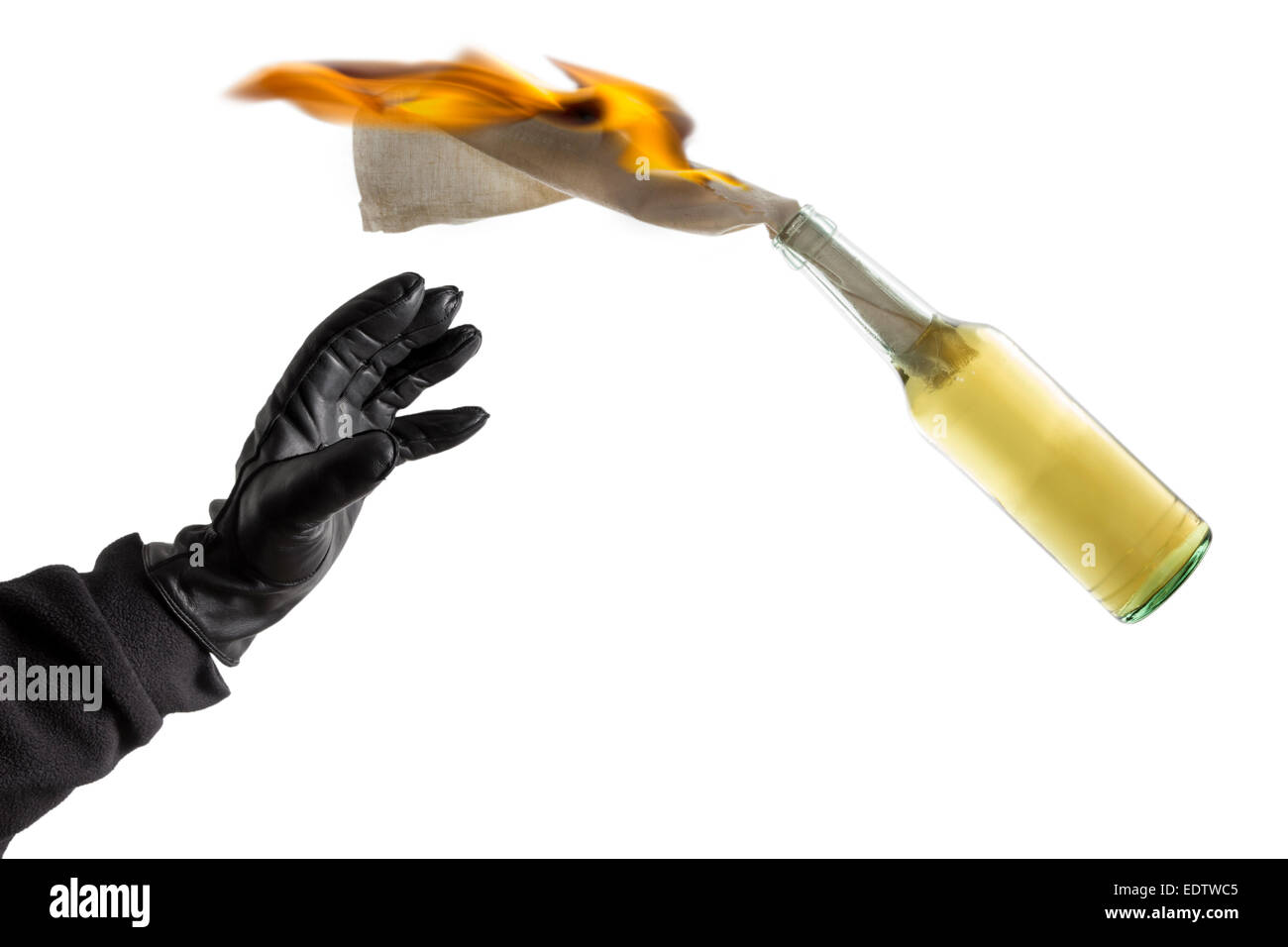Arm in black sleeve with black leather glove thwowing a Molotov Cocktail with burning fuse, isolated on white background - Stock Image