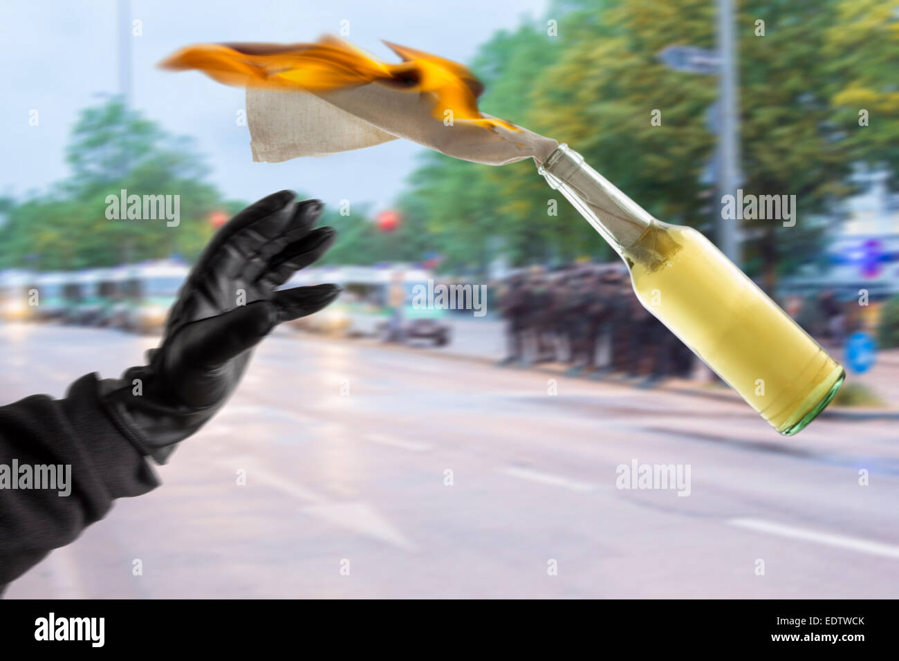 Arm in black sleeve with black leather glove thwowing a Molotov Cocktail with burning fuse, with police forces in - Stock Image