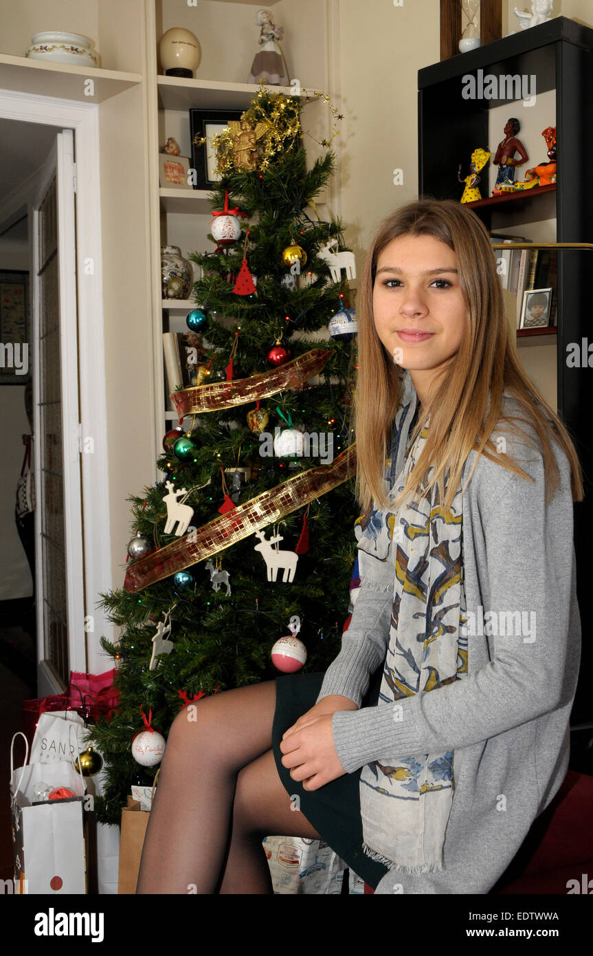 portrait of a sixties young lady on Christmas days, next to the x-mas tree. Spanish Catalan young lady from Barcelona - Stock Image