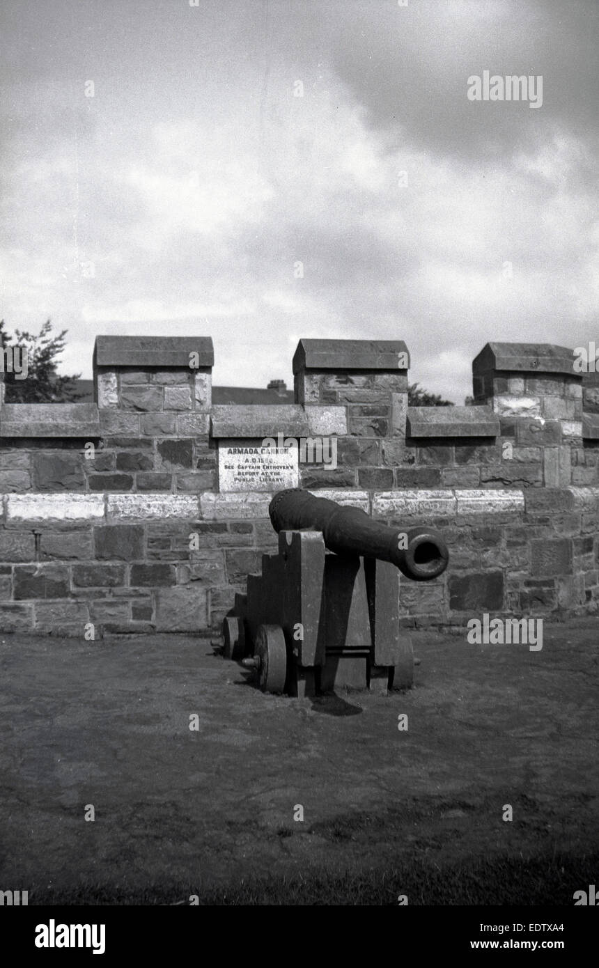 1930s historical, small portable cannon or artillery gun on wheels on top of a castle or turreted building. - Stock Image