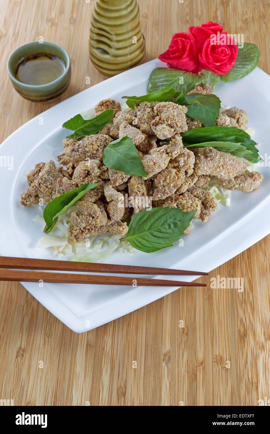 Vertical image of Chinese sliced fried cooked chicken in white dish with cup and ceramic drink pitcher in background - Stock Image
