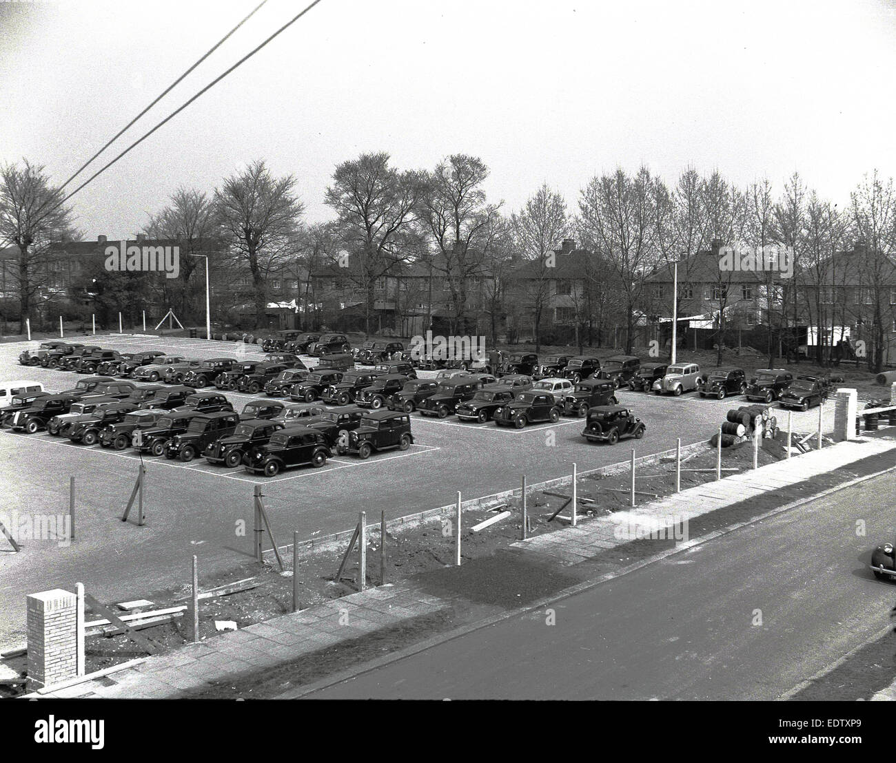 1940s historical picture showing a large number of cars of the era parked together in rows on a large plot outside - Stock Image