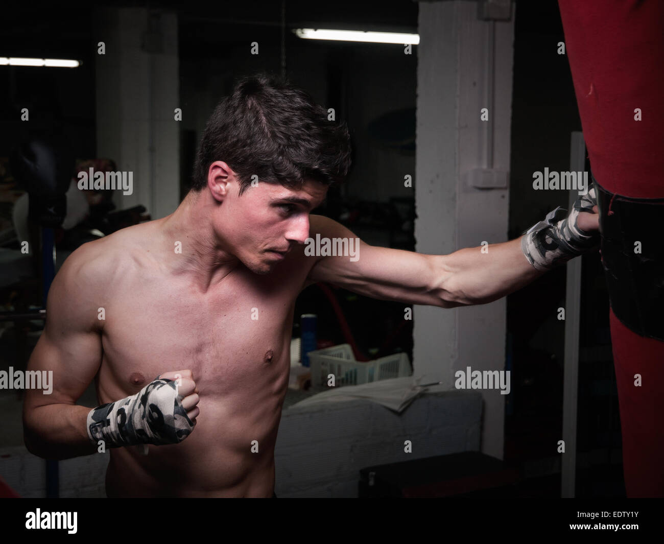 Young caucasian Boxer training with a punching bag in his home gym - Stock Image