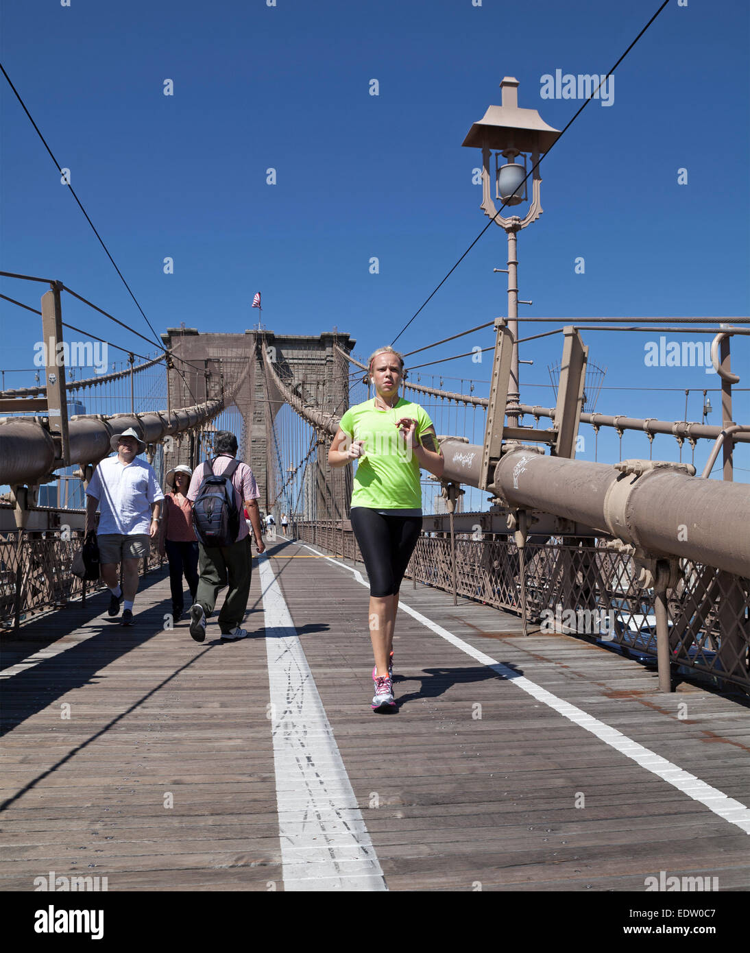 People walk, run, or ride bicycles separately from cars on the Brooklyn Bridge in New York City. - Stock Photo