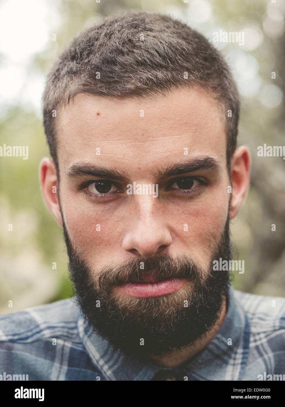 Hipster man portrait outdoors. Man is looking at camera. - Stock Image