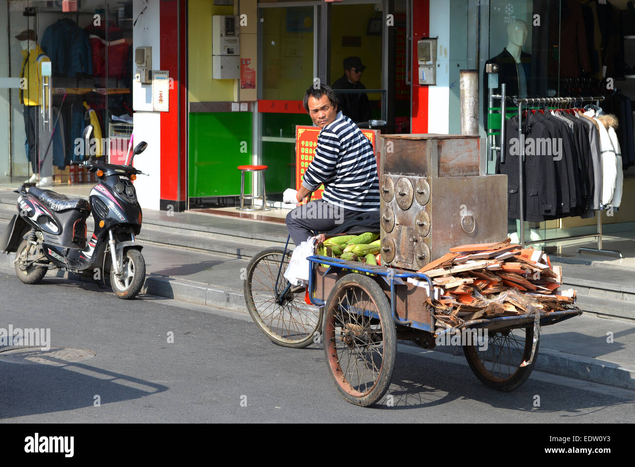 A man rides a portable roaster which allows him to sell roasted corn in Qingpu District of Shanghai. - Stock Image