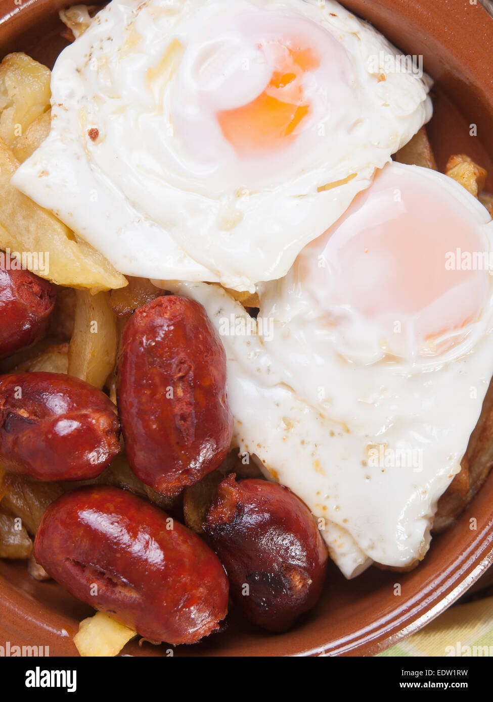 Eggs with french fries and small sausages. A typical spanish dish. - Stock Image