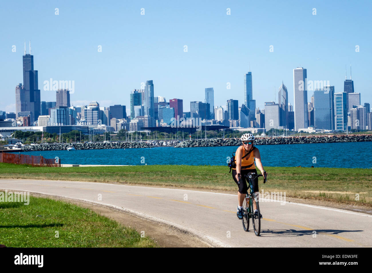 Chicago Illinois South Side Lake Michigan 39th Street Beach Lakefront Trail woman biker bicycle riding city skyline - Stock Image