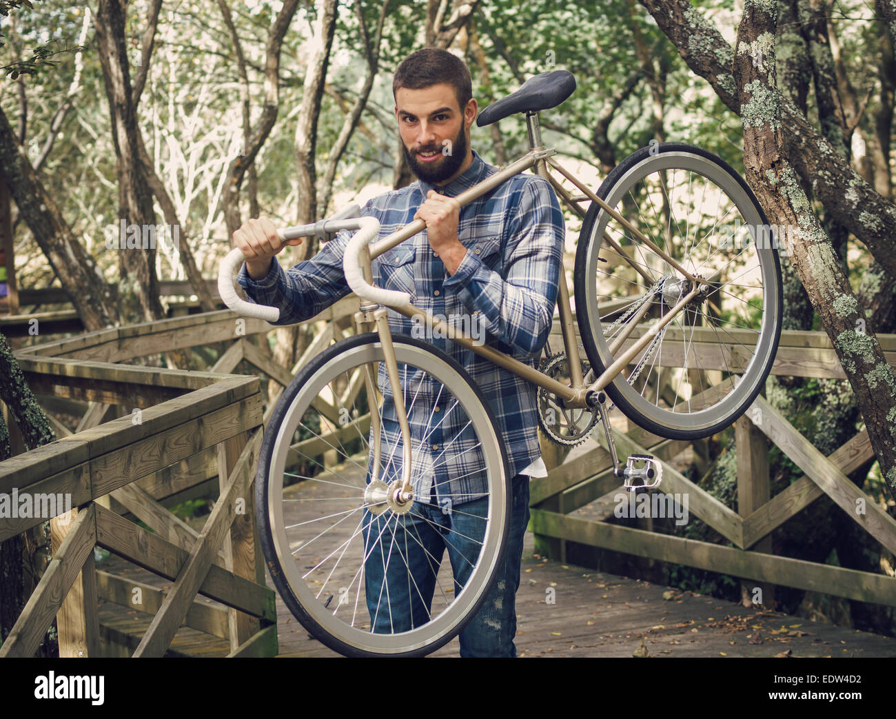 Hipster man holding his bicycle in a park outdoors - Stock Image