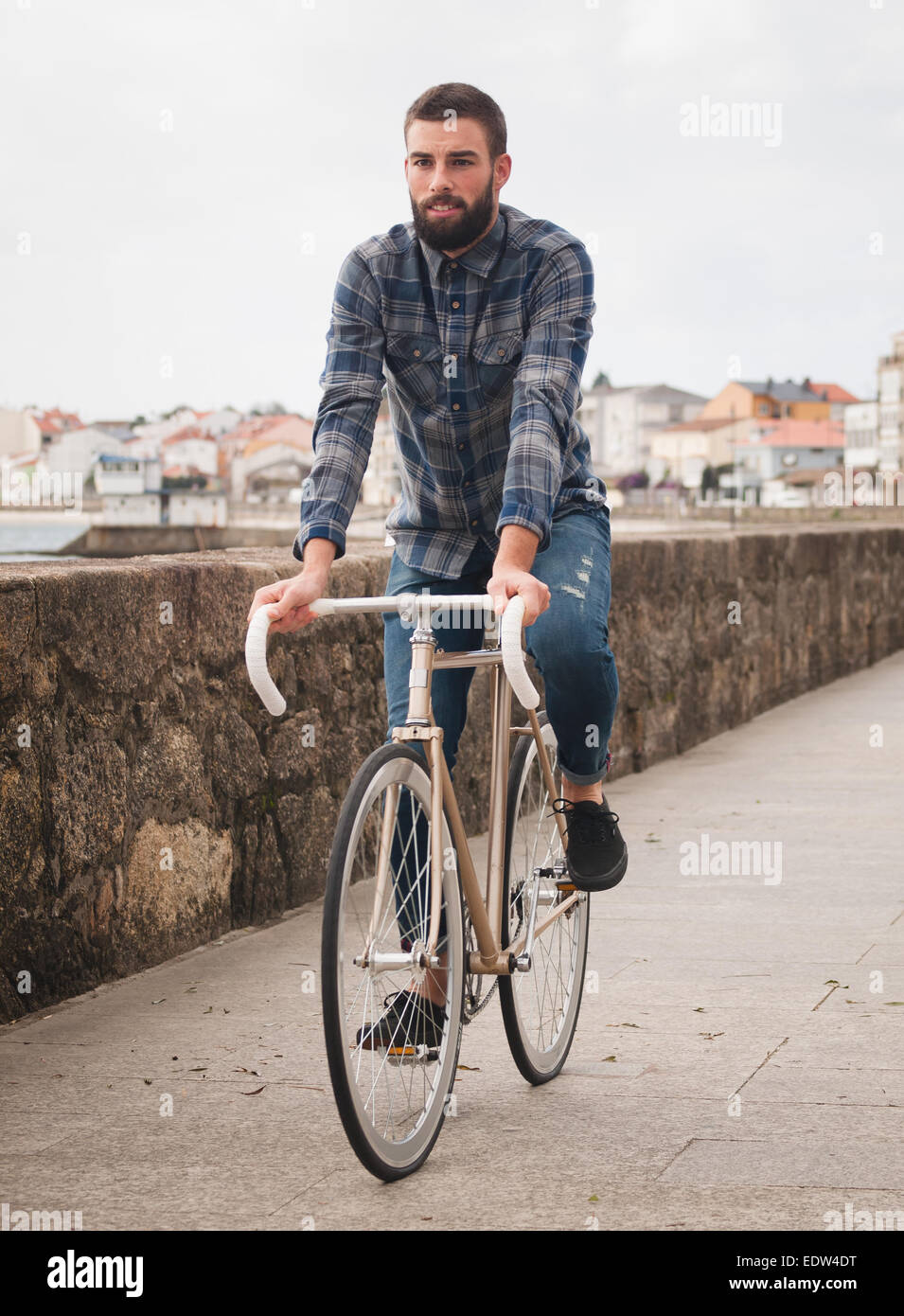 Hipster man riding in a fixie bike in the city. - Stock Image