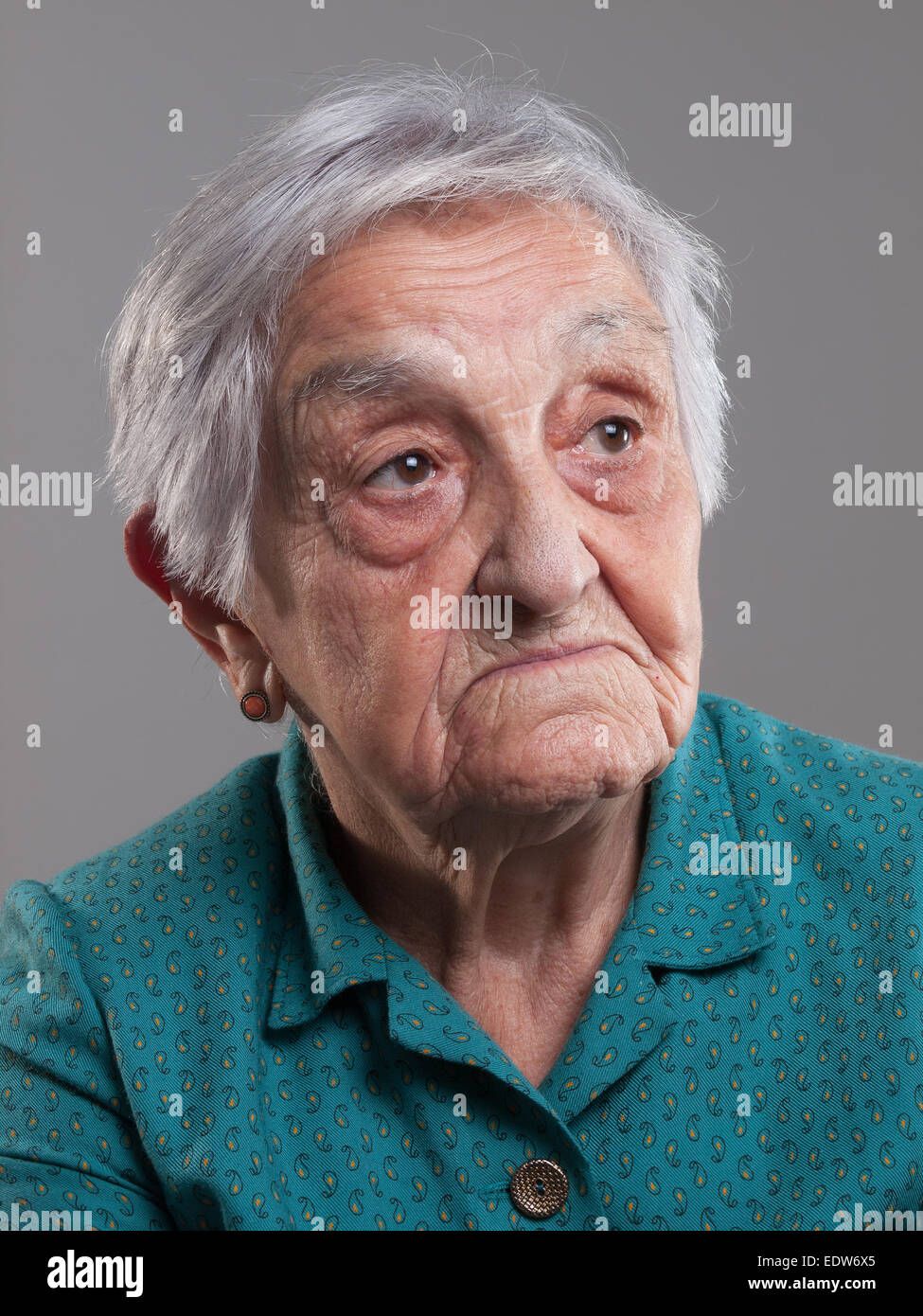 Portrait of an elderly woman in a studio shot and isolated on grey background - Stock Image