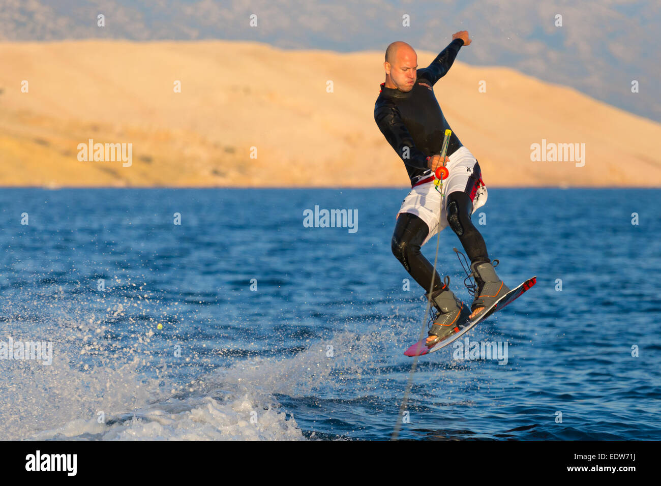 Wakeboarder in sunset. - Stock Image
