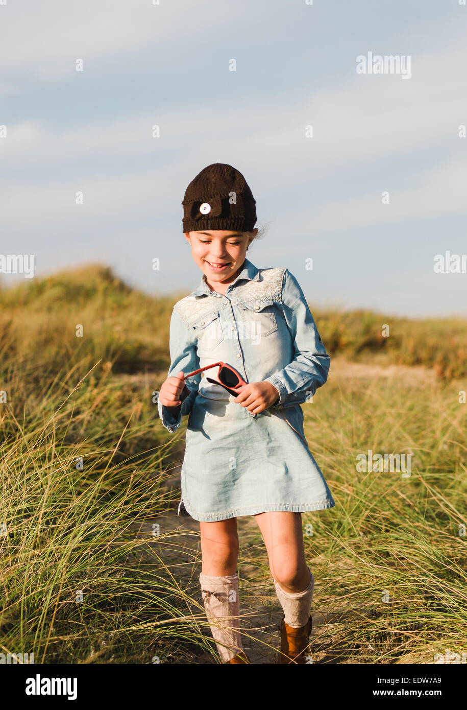Shy little girl on the beach in a sunny day - Stock Image