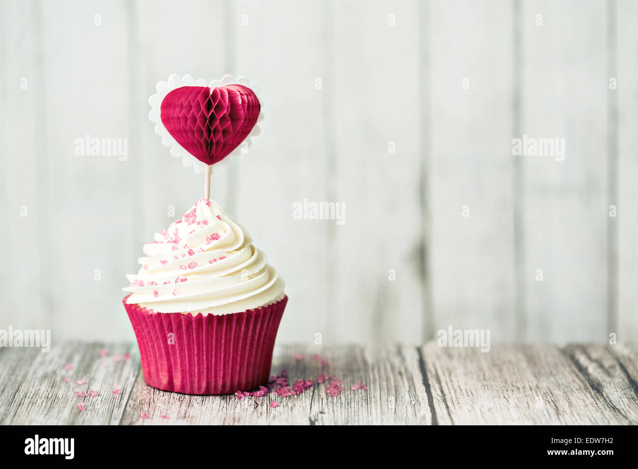 Cupcake decorated with a heart shaped cake pick - Stock Image